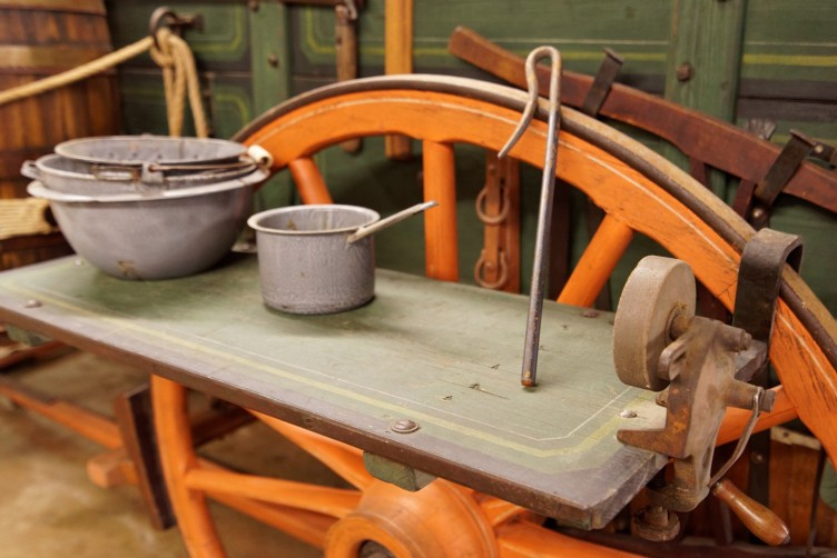 The chuck wagon's shelves hang over the wheels.  Notice the blade sharpener on the right.